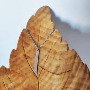 kaulakoru riipus hopean värinen jossa pieni kirkas kivi