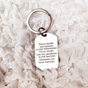 Valkoisella kangas alustalla hopean värinen avaimenperä